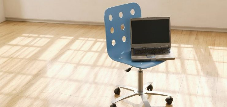 Laptop on a chair, in an empty office space