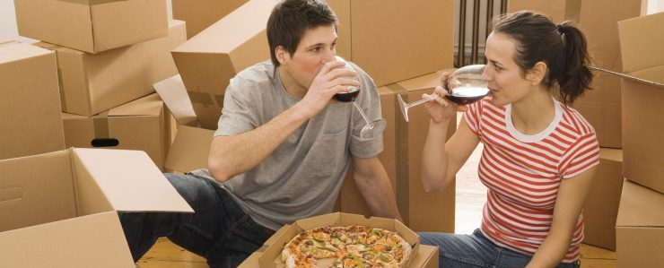 two people sharing a drink among moving boxes