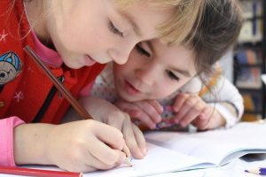 Two adorable kids drawing together