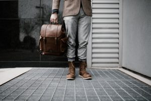 person holding brown leather bag