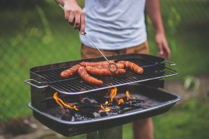 A man grilling sausages during a family cookout before the move