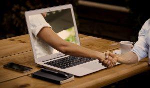 Handshake through a laptop illustration