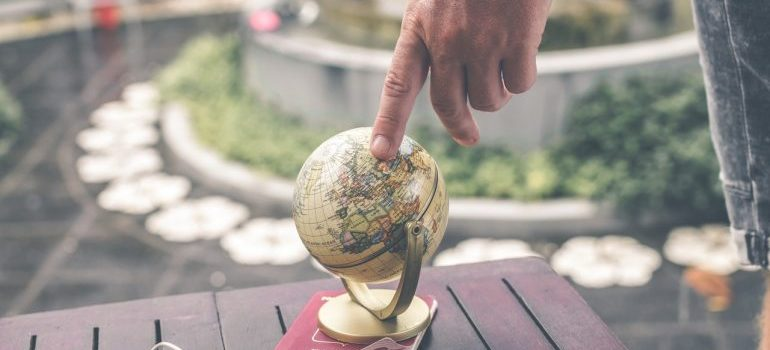 Person pointing a finger to a small globe