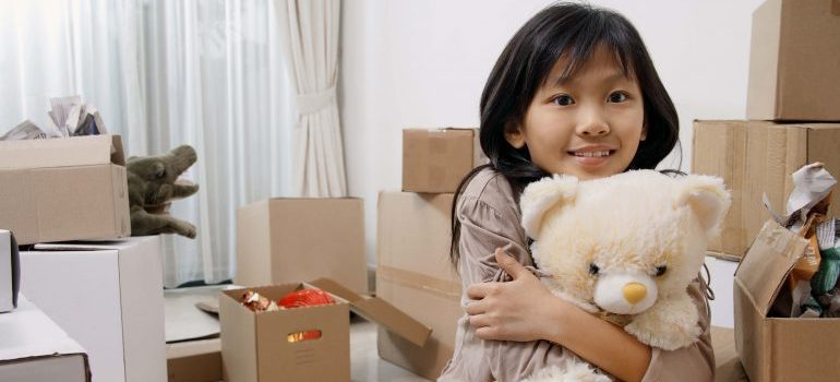 Girl holding teddy bear by moving boxes - movers Bradenton FL.