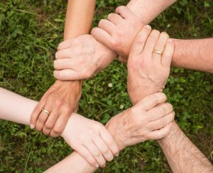 Five people holding each other by the wrists