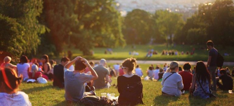 Group of people sitting on the grass in a park