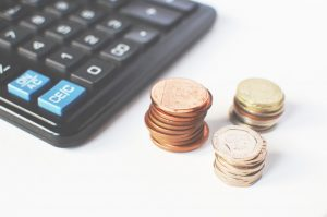 coins next to a calculator on the table