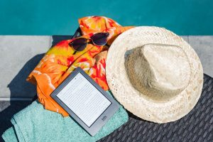 a hat, sunglasses and an e-reader next to a pool