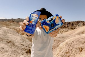 man holding blue camera and sunscreen