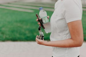 woman holding a plastic water bottle