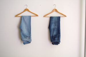 two pairs of jeans on hangers