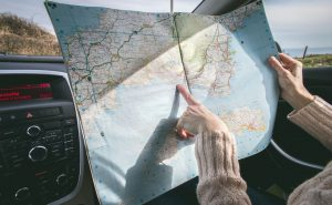 Person holding a map inside a car