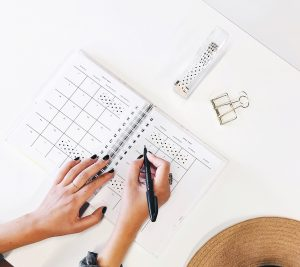 a picture of a woman holding a pen and writing a plan