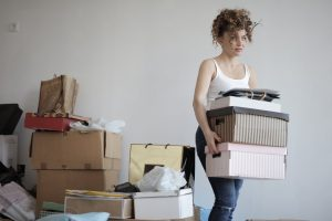 A woman carrying moving boxes