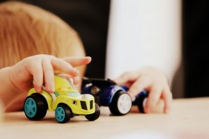 child playing with plastic toy cars