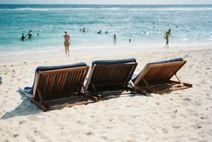 three wooden lounge chairs on a beach