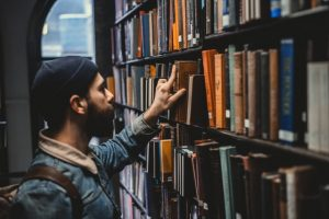 man browsing books in a library
