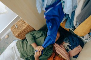 girl lying in a pile of clothes