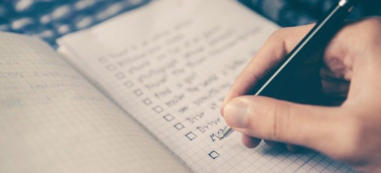 A person making a checklist - the way to prepare for your Wesley Chapel move.