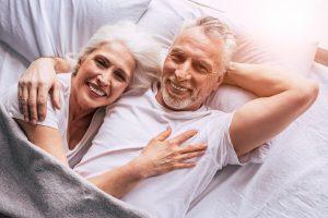 Elderly couple lying in bed.