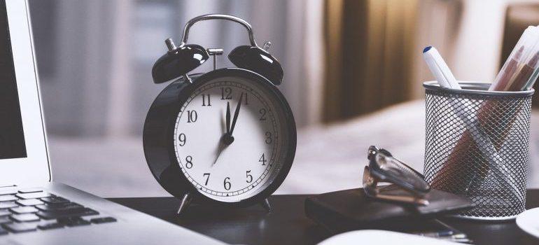 A black alarm clock on a desk.