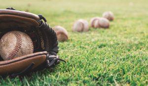 baseball mitt and balls on grass