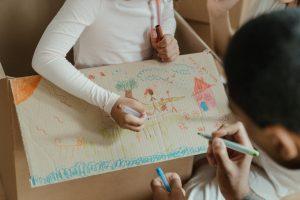 A girl drawing on a cardboard box