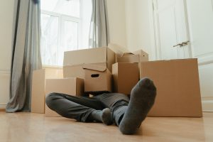a person in despair laying in moving boxes