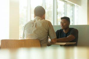 Two men talking during a meeting
