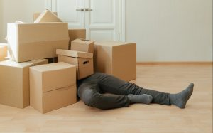 a man under of pile of moving boxes