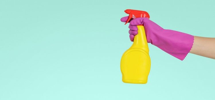 A hand in gloves holding a spraying chemical