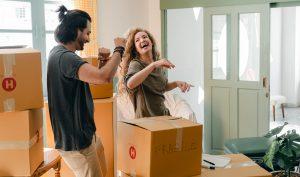 Happy couple unpacking boxes