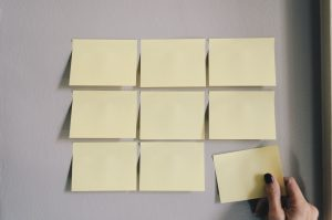 A woman putting post it notes on the wall showing that good organization is essential for moving to Clearwater FL