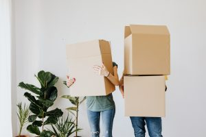 two people carrying cardboard moving boxes