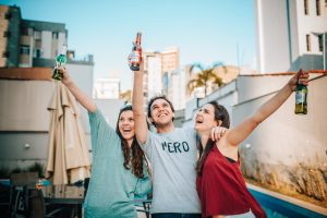 three friends enjoying their time and drinking beer as one of the weekend activities to try after moving to Florida