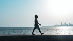 a man walking by a shore with the sun shining
