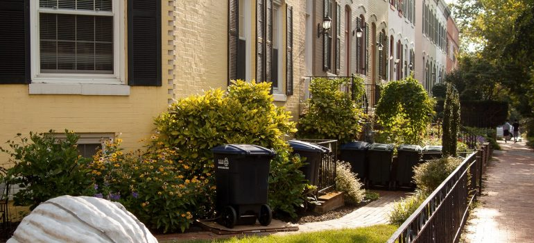 an outside of a home showing a pathway, a backyard and black trash cans