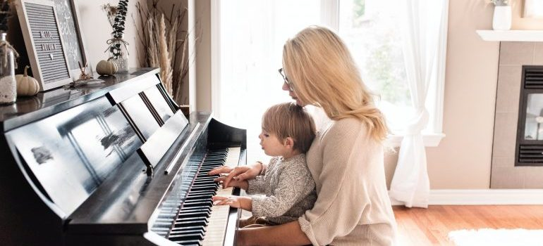Woman playing the piano with her child