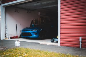 A garage with a blue car in it