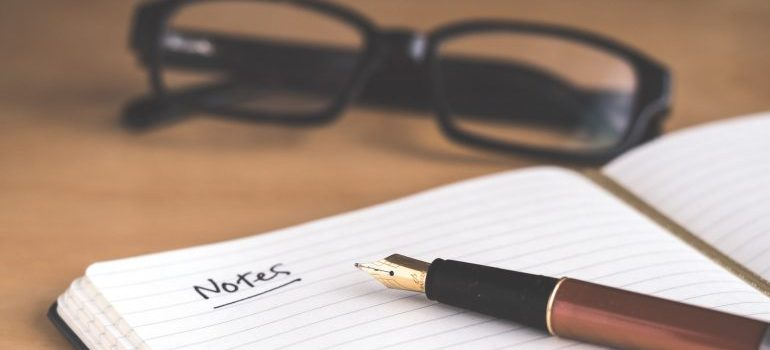 A notebook, glasses and a pencil on the desk