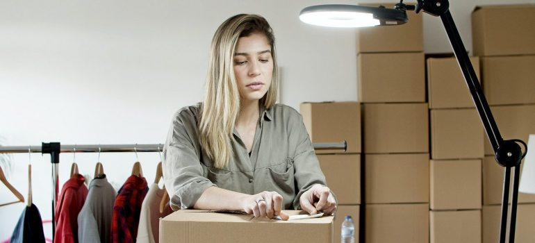 a woman taping a label on a cardboard box as should you as you pack for an interstate Florida move