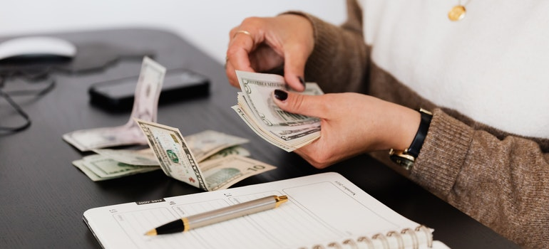 A woman is counting the money she will use to pay fees and bills.