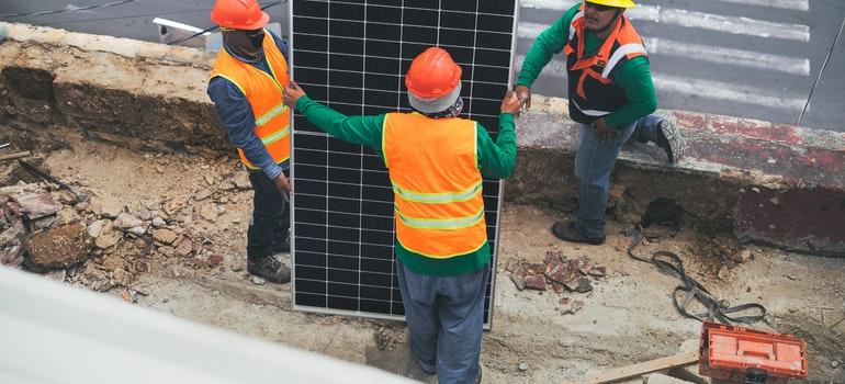 Three men are holding a solar panel.