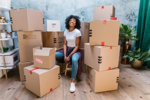 A girl sitting surrouneded by moving boxes