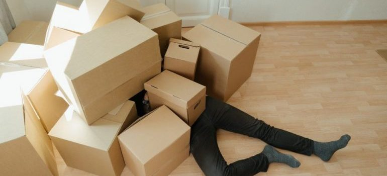 a man lying underneath a pile of cardboard boxes as a consequence of common mistakes people make.